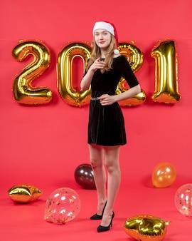 Vooraanzicht jonge dame in zwarte jurk wijzend op camera ballonnen op rood