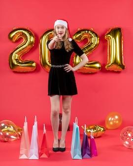 Vooraanzicht jonge dame in zwarte jurk wijzend op cameratassen op vloerballonnen op rood