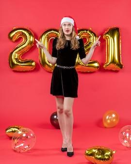 Vooraanzicht jonge dame in zwarte jurk wijzend op iets ballonnen op rood