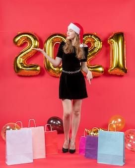 Vooraanzicht jonge dame in zwarte kledingzakken op vloerballons op rood