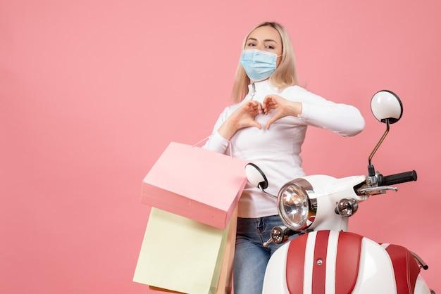 Vooraanzicht jonge dame met boodschappentassen hart teken staande in de buurt van bromfiets maken