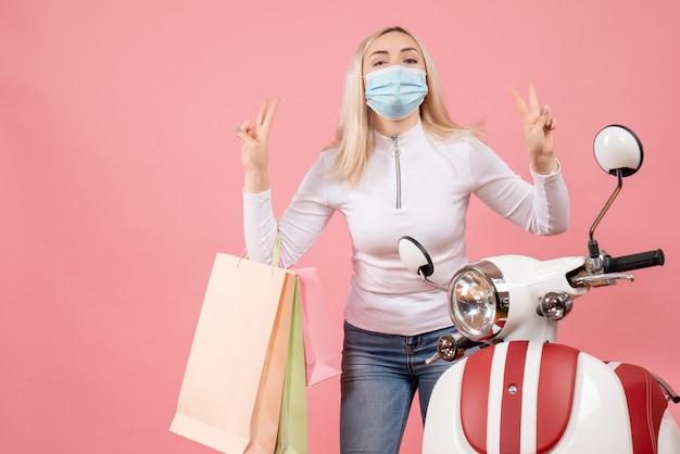 Vooraanzicht jonge dame met boodschappentassen overwinning teken maken in de buurt van bromfiets