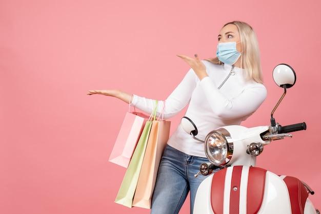 Vooraanzicht jonge dame met boodschappentassen permanent in de buurt van bromfiets
