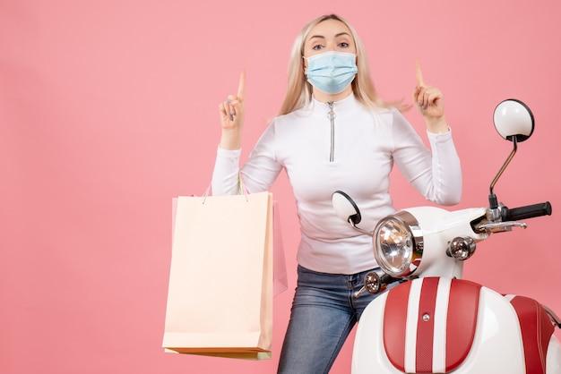 Vooraanzicht jonge dame met boodschappentassen vingers omhoog in de buurt van bromfiets