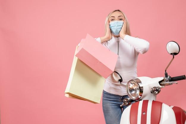 Vooraanzicht jonge dame met masker bedrijf boodschappentassen staande in de buurt van bromfiets