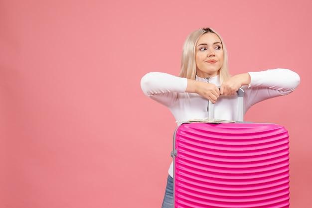 Vooraanzicht jonge dame met roze koffer