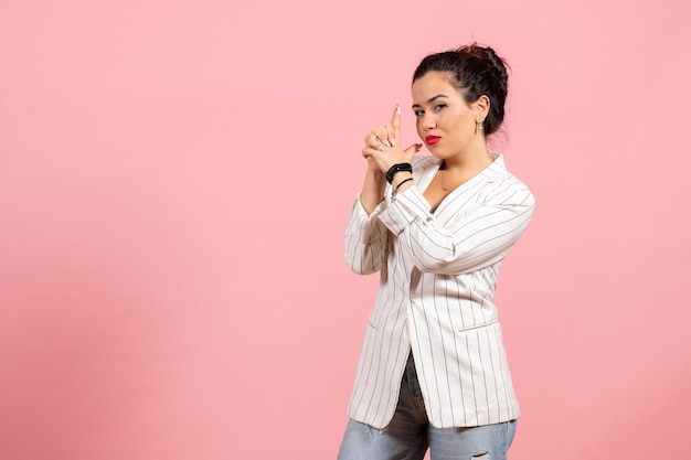 Vooraanzicht jonge dame met witte jas in pistool met pose op roze achtergrond dame emoties mode gevoel kleur woman