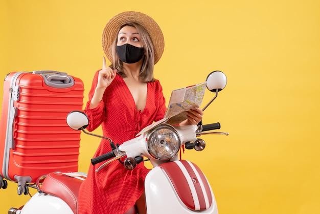 Vooraanzicht jonge dame met zwart masker op bromfiets met kaart omhoog kijkend