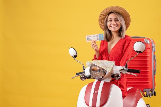 Vooraanzicht jonge dame op bromfiets met rode koffer die ticket omhoog houdt