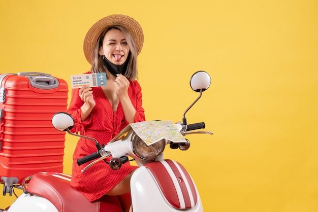 Vooraanzicht jonge dame op bromfiets met rode koffer die tong uitsteekt met ticket