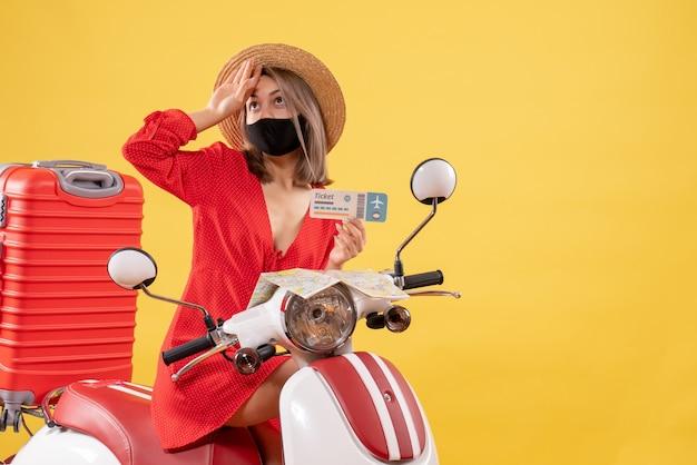 Vooraanzicht jonge dame op bromfiets met rode koffer met ticket hand op haar voorhoofd zetten