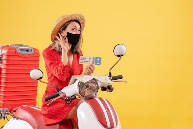 Vooraanzicht jonge dame op bromfiets met rode koffer met ticket luisterend naar iets