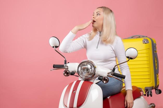 Vooraanzicht jonge dame op bromfiets roze muur benieuwd
