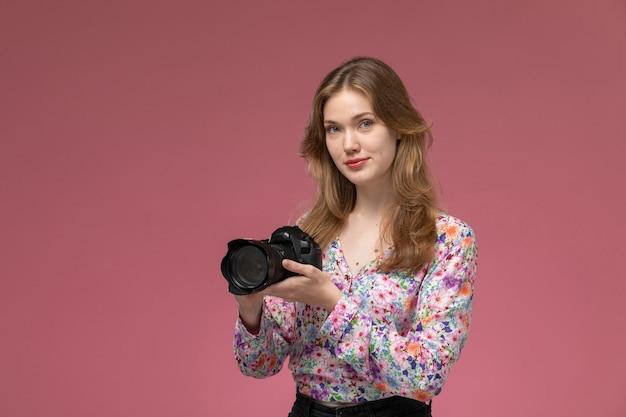 Vooraanzicht jonge dame poseren met haar fotocamera