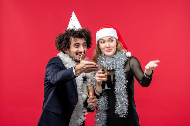 Vooraanzicht jonge gelukkige paar groet iemand op rode muur foto kerst liefde