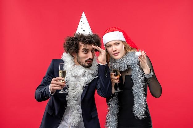 Vooraanzicht jonge gelukkige paar nieuwjaar vieren op de rode muur foto kerst liefde