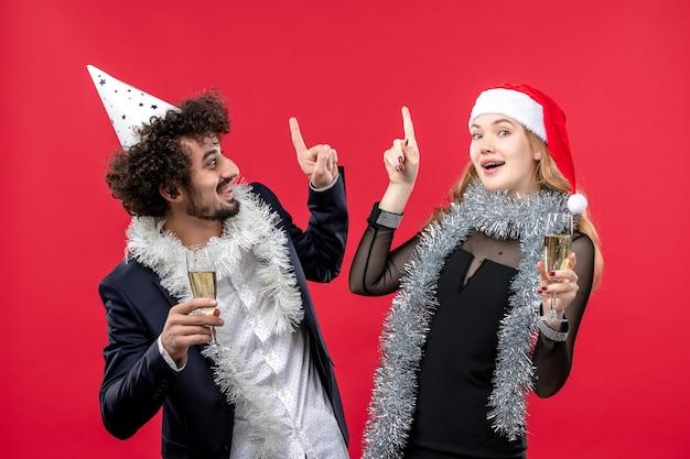 Vooraanzicht jonge gelukkige paar nieuwjaar vieren op de rode muur kerst love party