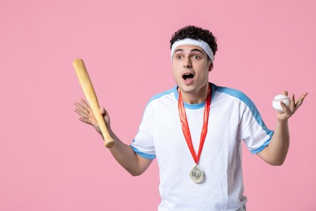 Vooraanzicht jonge honkbalspeler in sportkleren met medaille en knuppel