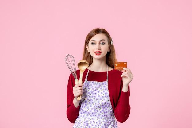 Vooraanzicht jonge huisvrouw met garde en bankkaart op roze achtergrond cake vrouw kleur taart koken keuken geld keuken eten