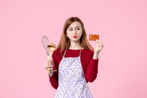 Vooraanzicht jonge huisvrouw met garde en bankkaart op roze achtergrond taart vrouw kleur taart winkelen koken geld keuken eten