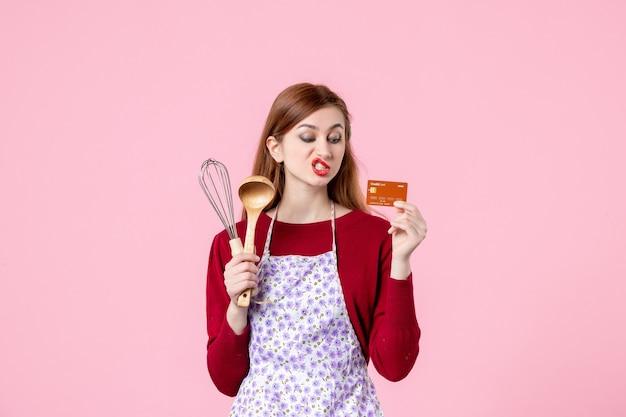 Vooraanzicht jonge huisvrouw met garde en bankkaart op roze achtergrond taart vrouw kleur taart winkelen koken keuken geld eten
