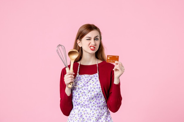 Vooraanzicht jonge huisvrouw met garde en bankkaart op roze achtergrond taart vrouw kleuren taart winkelen koken keuken geld keuken eten