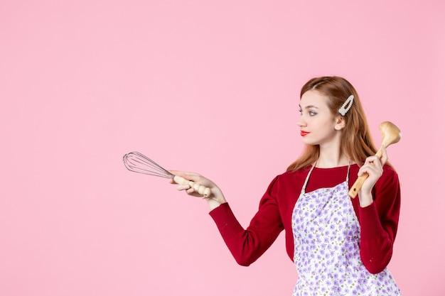Vooraanzicht jonge huisvrouw met garde en houten lepel op roze achtergrond vrouw taart beroep deeg horizontale keuken koken uniform cakes
