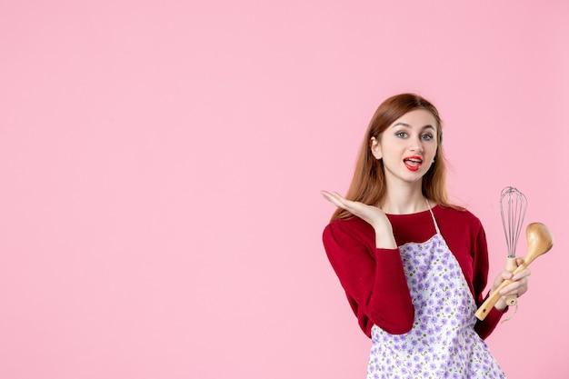 Vooraanzicht jonge huisvrouw poseren met garde en houten lepel op roze achtergrond vrouw taart beroep deeg horizontale keuken koken uniform cakes