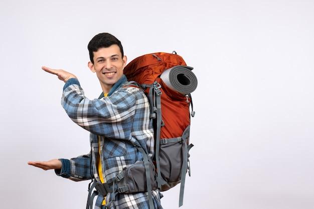 Vooraanzicht jonge kampeerder met rugzak die grootte met handen toont
