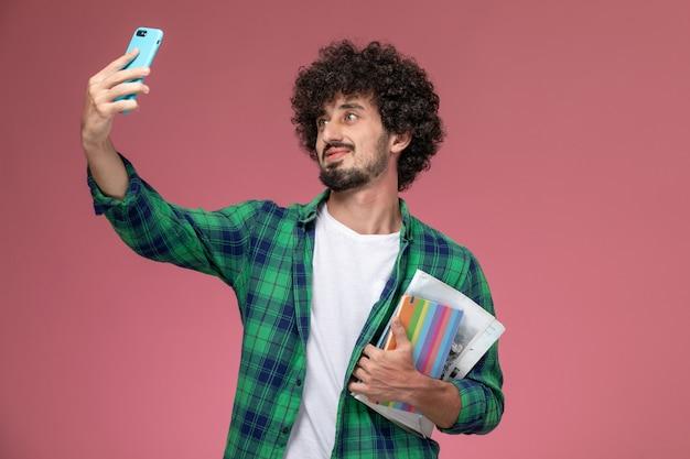 Vooraanzicht jonge kerel die een selfie met notitieboekjes neemt