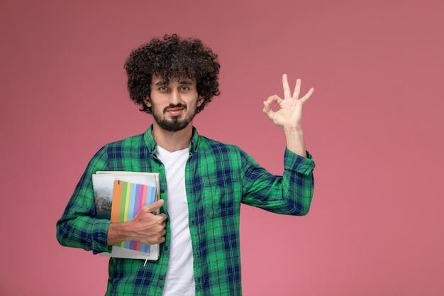 Vooraanzicht jonge kerel die ok gebaar met notitieboekjes geeft