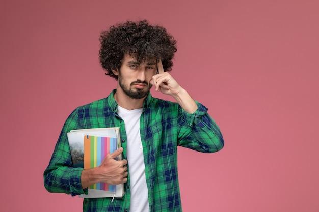 Vooraanzicht jonge kerel die over iets met notitieboekjes nadenkt