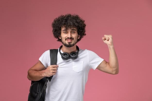 Vooraanzicht jonge kerel die zijn kracht toont en hoofdtelefoon gebruikt