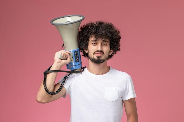 Vooraanzicht jonge kerel met handmicrofoon naast zijn hoofd