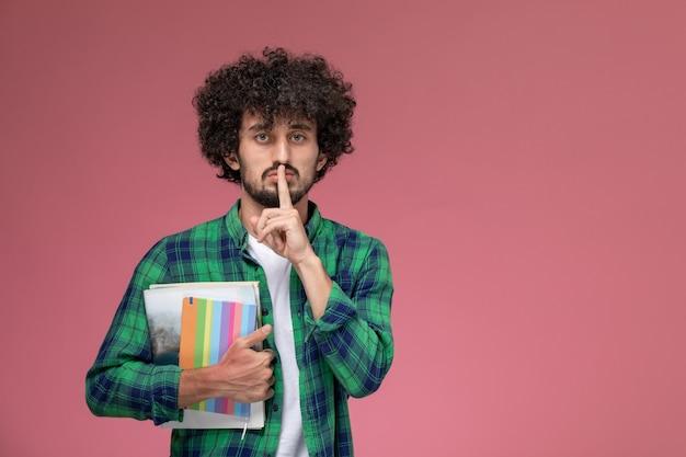 Vooraanzicht jonge kerel toont stil gebaar met notebooks