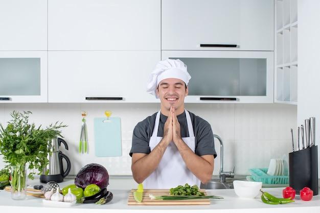 Vooraanzicht jonge kok in uniform die de handen in elkaar slaat en de ogen sluit