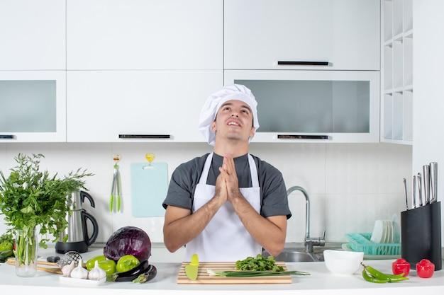 Vooraanzicht jonge kok in uniform die de handen ineen slaat en wenst