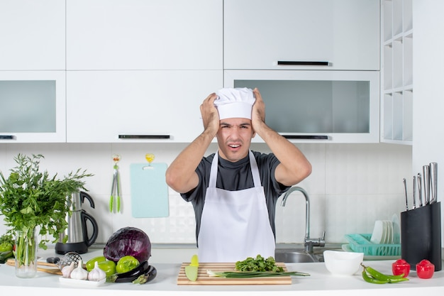 Vooraanzicht jonge kok in uniform die zijn hoofd vasthoudt