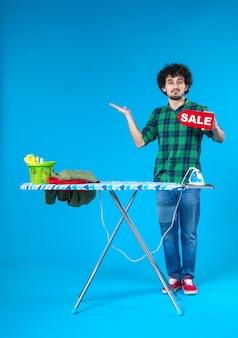Vooraanzicht jonge man bedrijf verkoop schrijven op blauwe achtergrond huis mens wasmachine kleur schoon huishoudelijk werk