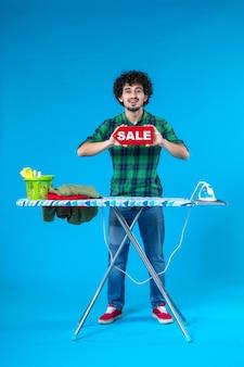 Vooraanzicht jonge man bedrijf verkoop schrijven op blauwe achtergrond huis mens wasmachine schoon winkelen huishoudelijk werk