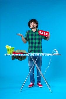 Vooraanzicht jonge man bedrijf verkoop schrijven op blauwe achtergrond kleur huis mens wasmachine schoon winkelen huishoudelijk werk was