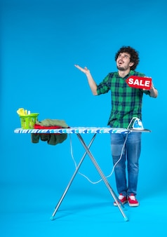 Vooraanzicht jonge man bedrijf verkoop schrijven op blauwe achtergrond mens wasmachine kleuren huis schoon winkelen huishoudelijk werk