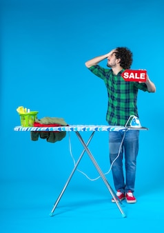 Vooraanzicht jonge man bedrijf verkoop schrijven op blauwe achtergrond menselijke wasmachine huishoudelijk werk kleur schoon winkelen
