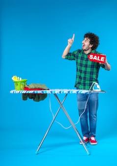 Vooraanzicht jonge man bedrijf verkoop schrijven op blauwe achtergrond menselijke wasmachine kleur huis schoon huishoudelijk werk