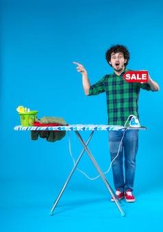Vooraanzicht jonge man bedrijf verkoop schrijven op blauwe achtergrond menselijke wasmachine kleur huis schoon winkelen