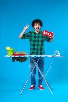 Vooraanzicht jonge man bedrijf verkoop schrijven op blauwe achtergrond menselijke wasmachine kleur schoon winkelen huishoudelijk werk