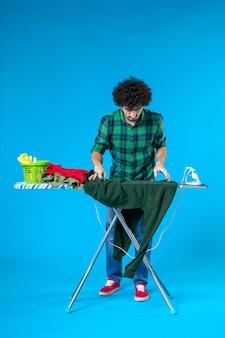 Vooraanzicht jonge man bereidt zich voor om groen shirt op blauwe achtergrond te strijken schone wasmachine huishoudelijk werk huis kleur mens