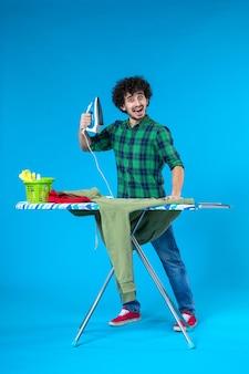 Vooraanzicht jonge man bereidt zich voor om groen shirt op blauwe achtergrond te strijken schone wasmachine huiskleur mens