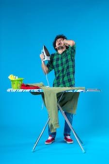 Vooraanzicht jonge man bereidt zich voor om groene trui op blauwe achtergrond te strijken schone wasmachine huishoudelijk werk huiskleuren mens