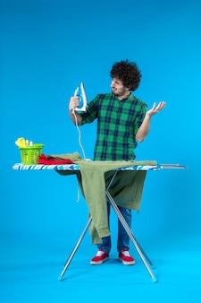 Vooraanzicht jonge man bereidt zich voor om groene trui op blauwe achtergrond te strijken schone wasmachine huiskleur menselijk huishoudelijk werk
